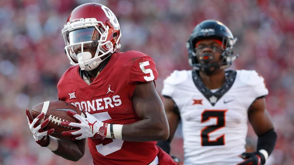 34b896566 Oklahoma wide receiver Marquise Brown (5) runs in for a touchdown ahead of  Oklahoma State cornerback Tanner McCalister (2) in the second quarter of an  NCAA ...